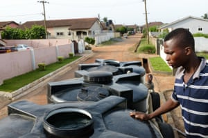 Shakibu prepares to pump water into a storage tank at a customer's home in an wealthy suburb of Ghana's capital, Accra