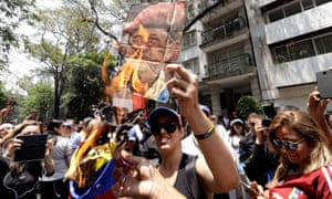 Supporters of Venezuelan opposition leader Juan Guaidó burn a picture of late President Hugo Chavez during a protest outside the Venezuelan embassy in Mexico City on Tuesday.
