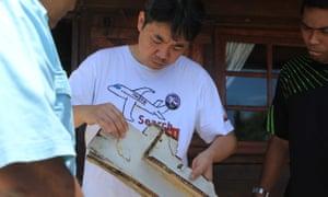 Jiang Hui examines some suspected debris from the plane that was found in Madagascar last year.