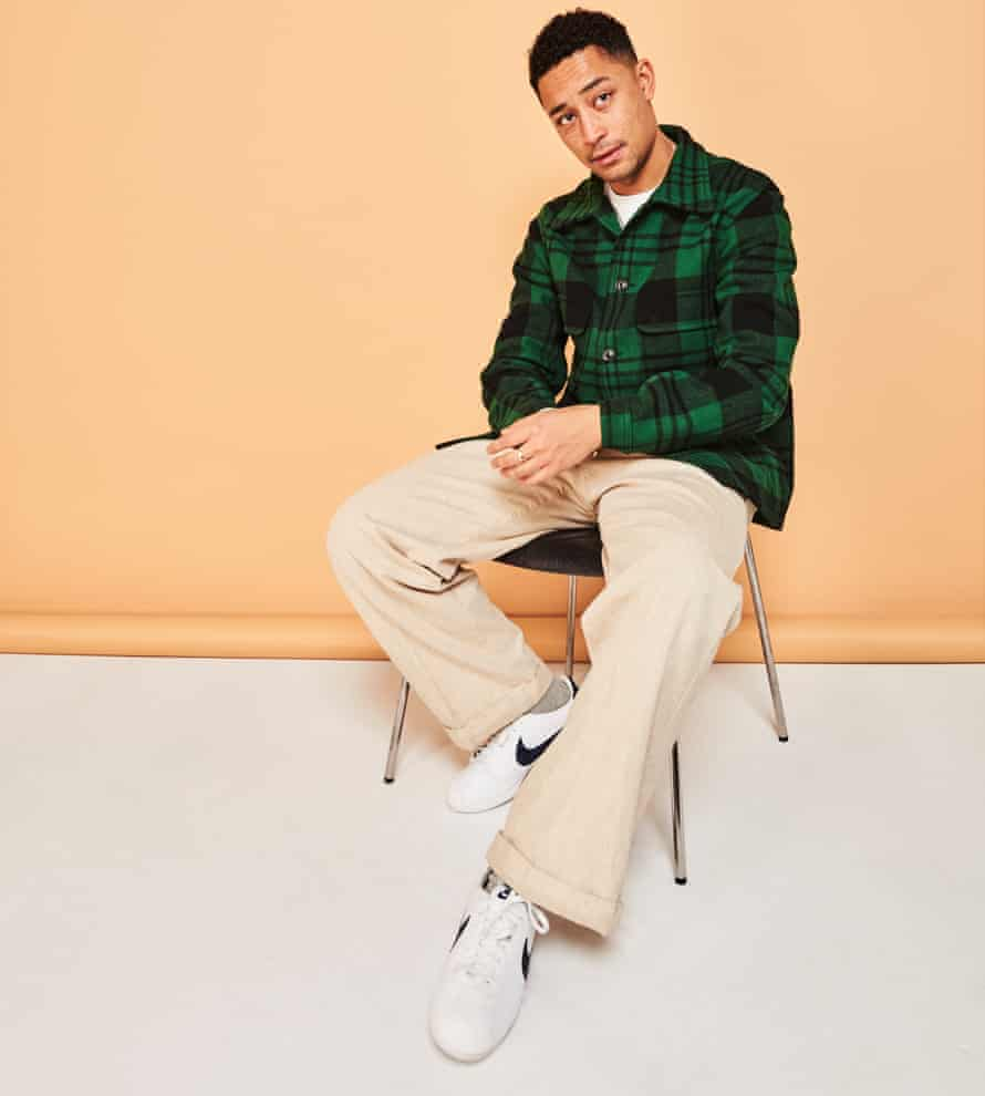 Coyle-Larner sitting on a chair in pale trousers, a green check shirt and white trainers