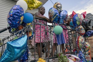 New York, US Melodi Butler stands on a stoop beside a makeshift memorial at the scene where 10-year old Justin Wallace was shot and killed in the Rockaway section of the Queens borough of New York
