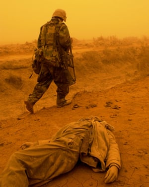 A US marine passes the corpse of an Iraqi soldier killed during a failed ambush on US forces marching to Baghdad