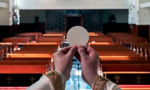 Priest's hands holding communion wafer in front of a view of empty church pews
