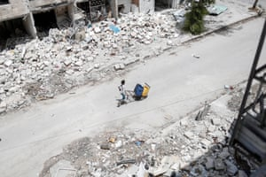 A boy pushes his cart through the bombed-out Aleppo neighbourhood of Hanano