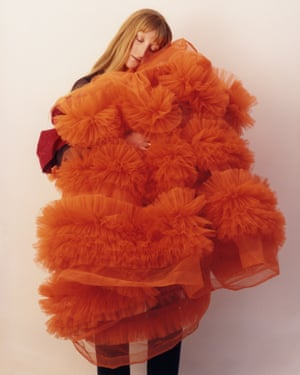Clutching a large, red fluffy  dress