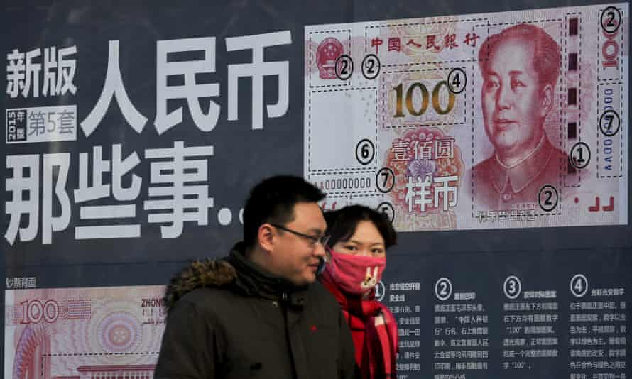 A couple walk past a display showing the security features of the new 100 Yuan note in Beijing, Monday, 11 January, 2016. China's exports dropped 2% in April.