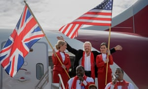 Richard Branson, centre, with two members of the Virgin Atlantic flight crew, with UK and US flags, in 2014