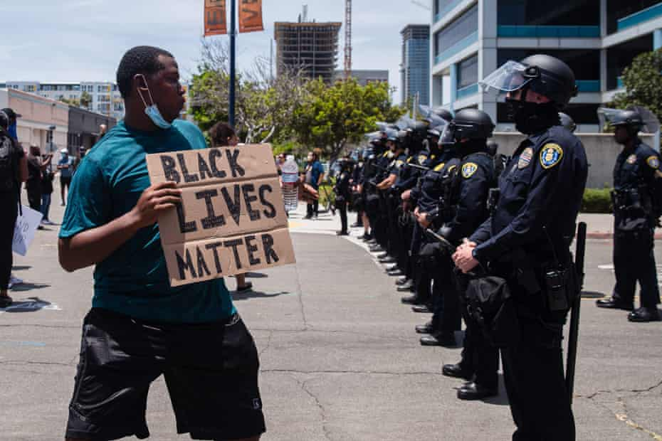 A man holds a Black Lives Matter sign in front of a line of San Diego police officers on 31 May 2020.