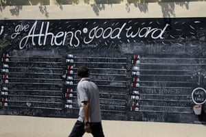 A pedestrian looks at a board where people can write their comments about the Greek capital, displayed on a wall in Athens, Monday, July 27, 2015. The government has already begun imposing new austerity measures demanded in return for the new bailout — but had relied on support from opposition parties after nearly a quarter of lawmakers in the ruling Syriza party opposed him. (AP Photo/Thanassis Stavrakis)