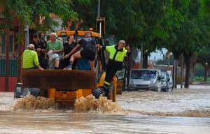 People hitch a ride on an excavator in Redovan