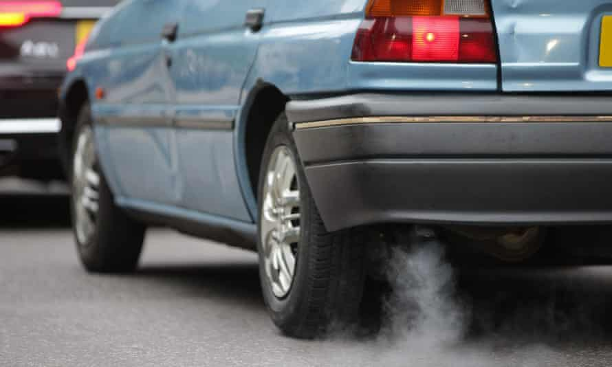 A car emits fumes from its exhaust as it waits in traffic in central London