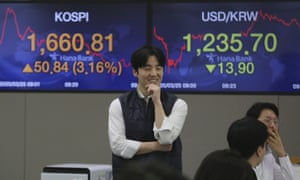 A currency trader smiles at the foreign exchange dealing room of the KEB Hana Bank headquarters in Seoul, South Korea