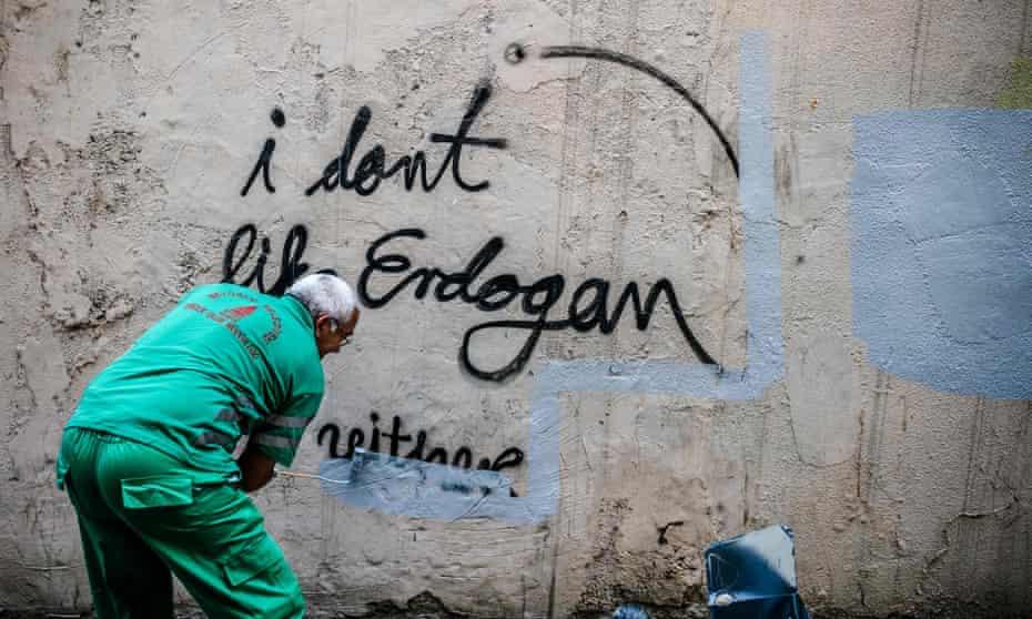 A municipal worker covers graffiti near the pro-Kurdish Özgür Gündem newspaper's Istanbul headquarters in June