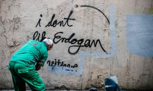 A municipal worker covers graffiti on a wall with grey paint in Istanbul, Turkey.