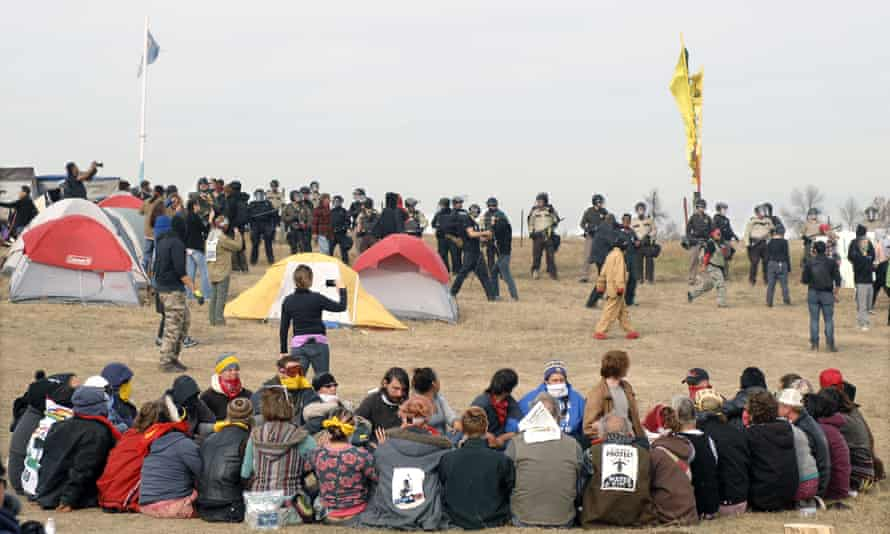 Dakota Access pipeline protesters sit in a prayer circle as a line of law enforcement officers make their way across the camp to remove them last week.