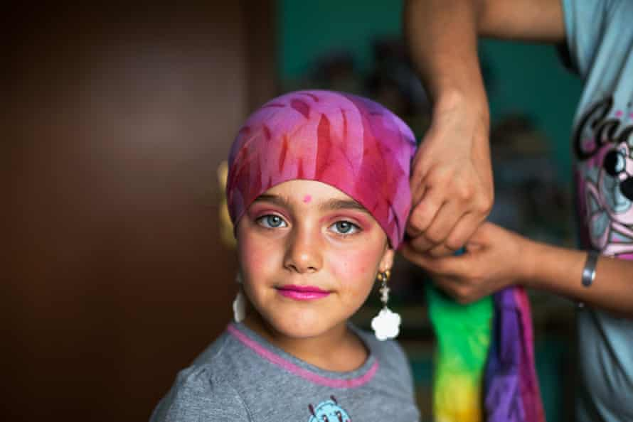 Seven year-old Zayneb plays dress-up with her mother