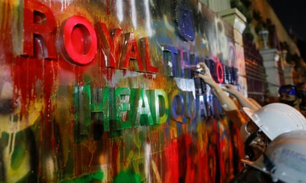 Pro-democracy protesters spray paint signage on Thailand's police headquarters
