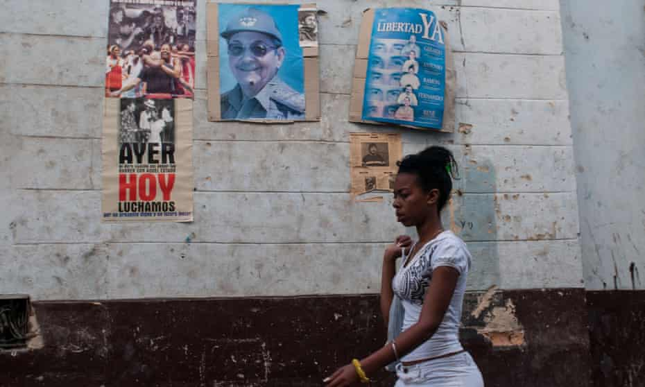 woman walks by Raul Castro posters