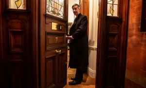 Jacob Rees Mogg opens the door of his Westminster home on Tuesday to his guests after the defeat of May's Brexit deal.