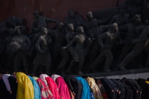 People bow as they pay their respects before the statues of Kim Il-sung and Kim Jong-il