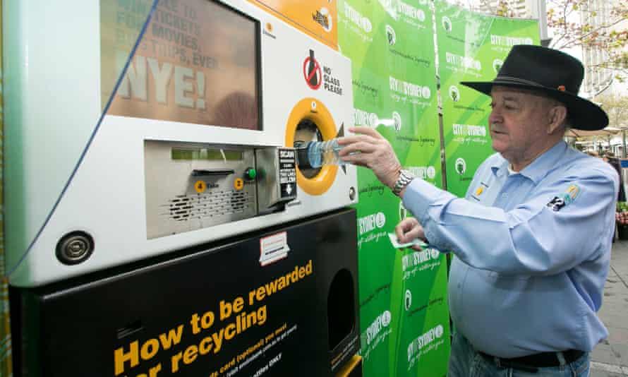 Ian Keirnan of Clean Up Australia depositing a plastic bottle into the an Envirobank reverse vending recycling machine, Sydney