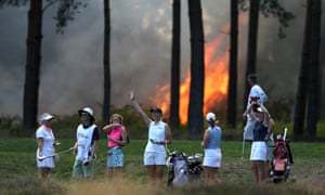 Golfers Sophie Powell, Cara Gainer, Gabriella Cowley and their caddies look on as a fire nears the 10th hole during the Rose Ladies Series at Wentworth golf club
