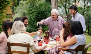 Senior man pouring wine at family meal