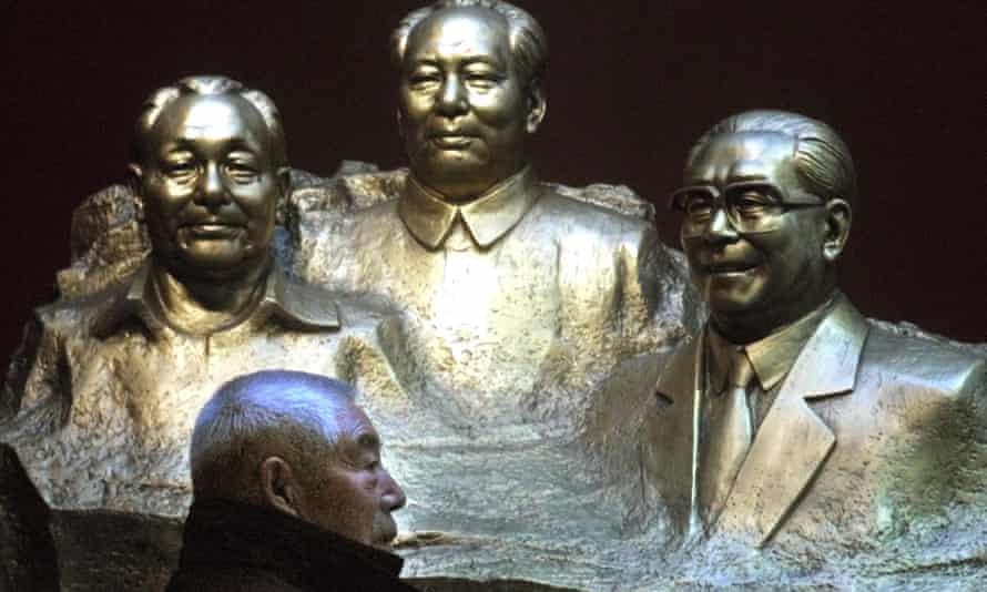 A man walks past busts of Deng Xiaoping, Mao Zedong Jiang Zemin