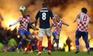 Darijo Srna, left, heads the ball away during a game against Scotland.