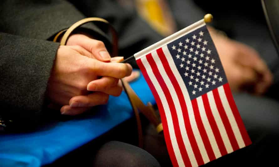 A woman holds a US Flag during a naturalization ceremony in Lowell, Massachusetts, this month.