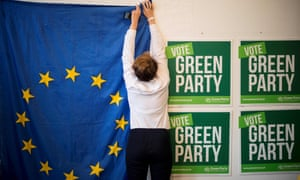 Volunteers hang a EU flag as they prepare the room for the launch of the Green Party's European election campaign.