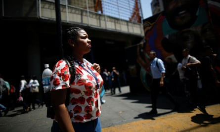 A woman stands in front of a closed metro station during a blackout in Caracas on 25 March.