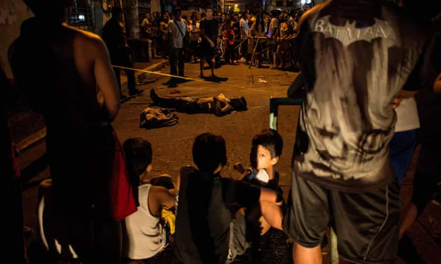 Local residents gather around the body of an alleged drug user, killed by unidentified assailants, in Manila in 2017
