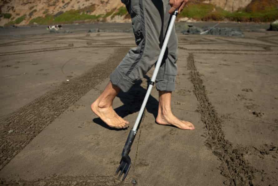 Amador makes his artwork by raking the sand.