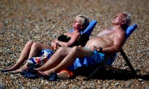 A couple sunbathe in Brighton.