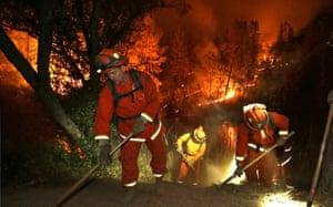 Firefighters create a firebreak near a home in Middletown