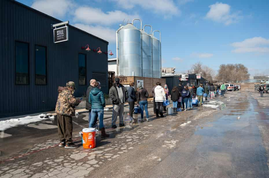 People wait in line at St Elmo Brewery for free potable water in Austin.