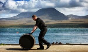 A still man rolls a whisky barrel at Diageo's Caol Ila distillery on Islay.