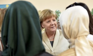 Angela Merkel speaks with women at a refugee camp