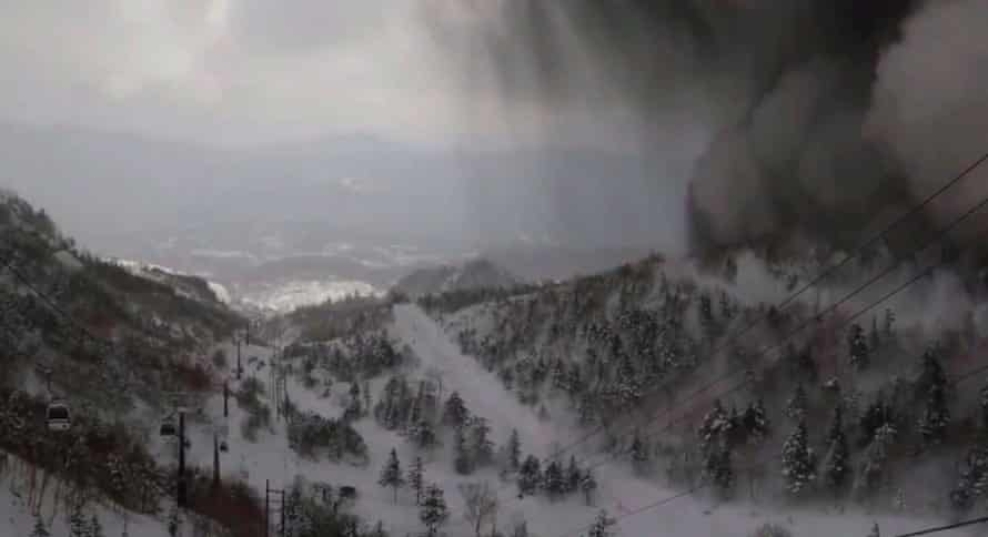 A black cloud moving in from the top right corner of the frame following a volcanic eruption nearby and a near-simultaneous avalanche, near Mount Kusatsu-Shirane.