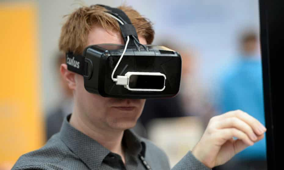 A visitor uses Oculus virtual reality goggles at a tech conference.