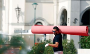 A worker at the Venice Film Festival prepares to roll out the red carpet for the international film community.