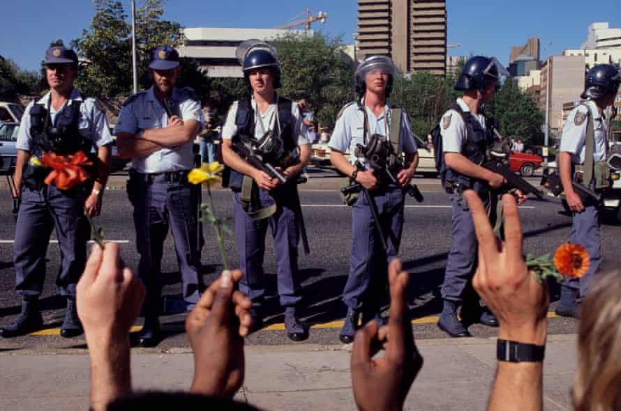 Heavily armed police officers watch as anti-apartheid student protesters at the University of Witwatersrand hold flowers and flash peace signs in 1989.