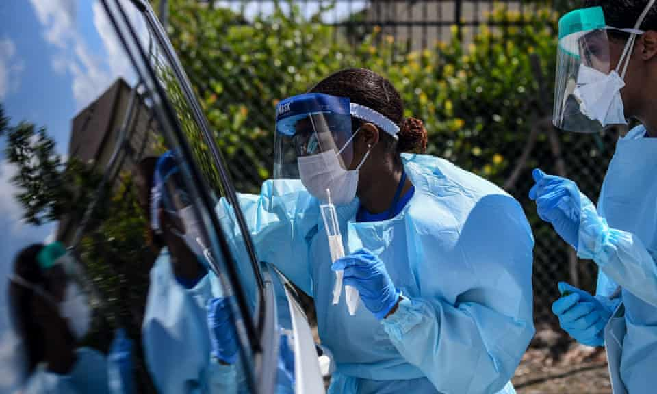 """Medical personnels take medical samples of patients at a """"drive-thru"""" coronavirus testing lab in Maryland."""