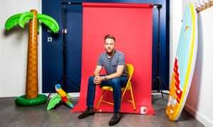 Tom Blomfield, in jeans and a t-shirt, sitting on a yellow metal chair, a red screen behind him, and with a blow-up palm tree and parrot one side of him, and a blow-up surf board propped up the other