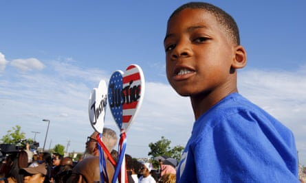 Aarington Traylor holds signs calling for justice during a protest against police behaviour in McKinney, Texas.