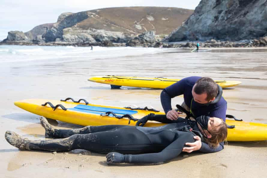 The instructor displays how to handle a patient after recovering them from the water.