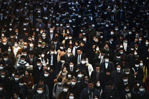 Mask-clad commuters make their way to work during morning rush hour at the Shinagawa train station in Tokyo. Tokyo's key Nikkei index plunged nearly 3% at the open on 28 February after the US and European sell-offs with investors worried about the economic impact of the coronavirus outbreak.