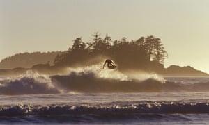 Canada, British Columbia, surfer at sunset launching some air, Tofino, Vancouver Island, British Columbia, Canada.