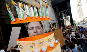 Fired FBI director James Comey emerges from a cake during a protest held on Trump's birthday.
